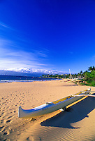 Outrigger canoe on sand on Kapalua beach with deep blue sky