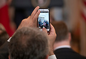 A reporter takes an iPhone photo as United States President Donald J. Trump, right, and Prime Minister Giuseppe Conte of Italy, left, hold a joint press conference in the East Room of the White House in Washington, DC on Monday, July 30, 2018.<br /> Credit: Ron Sachs / CNP