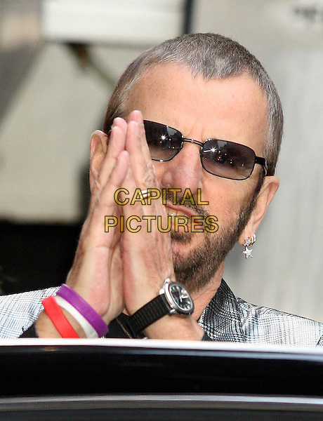 BARABARA BACH & RINGO STARR.At The David Letterman Show in New York..June16, 2005.half length silver suit jacket hands together praying gesture standing behind car purple red white rubber bracelets married husband wife.www.capitalpictures.com.sales@capitalpictures.com.©Capital Pictures