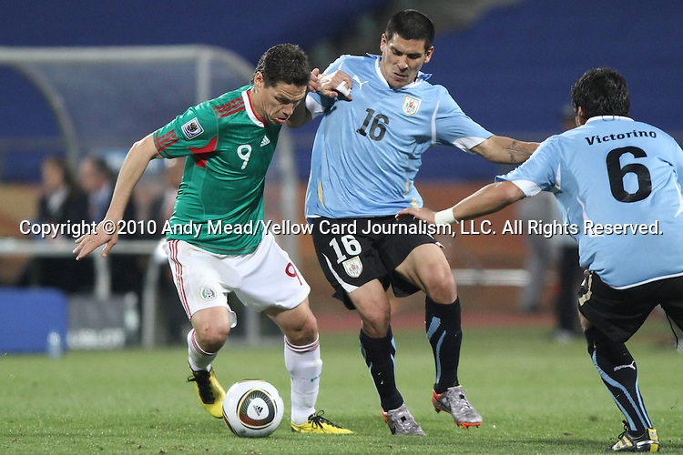 22 JUN 2010: Guillermo Franco (MEX) (9) and Maximiliano Pereira (URU) (16). The Uruguay National Team defeated the Mexico National Team 1-0 at Royal Bafokeng Stadium in Rustenburg, South Africa in a 2010 FIFA World Cup Group A match.