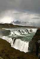 The waterfall at Gullfoss is Iceland's best-known natural wonder. The overcast sky and light rain enhanced the already eerie quality of the atmosphere as I approached the spectacular double falls where the River Hvítá pours into a narrow ravine. The path winds along the river to a rocky overlook revealing a dramatic vista at the edge of the breathtaking falls.