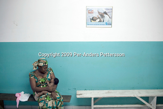 DOUALA, CAMEROON - AUGUST 10: A woman sits with her baby at the maternity ward at Bonassama hospital on August 10, 2009 in Douala, Cameroon. The ward is full of advertising for Nestle and Bledina products, something that is not allowed in the country. Many midwifes and maternity staff is encouraging women to use powder milk rather than breast milk after the women has give birth. (Photo by Per-Anders Pettersson)......
