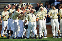 Joey Rodriguez (7) of the Wake Forest Demon Deacons is congratulated by his teammates after hitting a 3-run home run against the Virginia Cavaliers at Wake Forest Baseball Park on April 6, 2013 in Winston-Salem, North Carolina.  (Brian Westerholt/Four Seam Images)