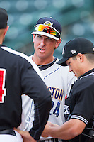 Charleston RiverDogs infield coach Justin Tordi (24) brings the lineup to home plate umpire Derek Gonzales \pg\ Hickory Crawdads at L.P. Frans Stadium on June 2, 2014 in Hickory, North Carolina.  The Crawdads defeated the RiverDogs 9-6.  (Brian Westerholt/Four Seam Images)