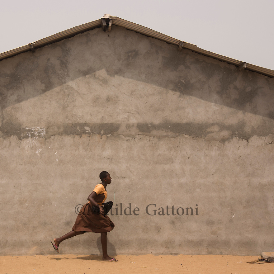 Ghana - Fuveme - A schoolgirl runs for cover as the ocean waves start flooding the village.