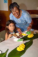 A local woman smiles as a young girl gets ready to eat her luau plate at the annual fundraiser at the Academy of the Pacific in Honolulu.