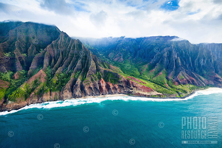 An aerial view of Na Pali Coast on Kaua'i includes a long stretch of beach, red dirt and clouds touching mountain tops.