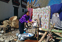 Domestic chores without modern electrical appliances - a woman washing up by hand using cold water from an outdoor tap.  Street scene in Bhutan.