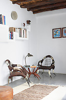 Two designer chairs made from animal horn and skins furnish a corner of this sitting room