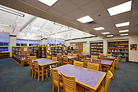 Middle school library with vaulted and flat ceiling, wood tables, contemporary carpeting and lighting fixtures.
