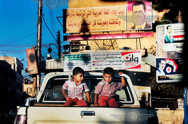 Two brothers sit in the back of a pickup driving in the city centre in the area who is still under control of the Assad regime. Billboard portraits of Assad line the roadside.