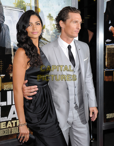 "CAMILA ALVES & MATTHEW McCONAUGHEY.Screening of ""The Lincoln Lawyer"" held at The Arclight Theatre in Hollywood, California, USA..March 10th, 2011.half length black one shoulder dress silk satin grey gray suit waistcoat couple arm around waist profile                                               .CAP/RKE/DVS.©DVS/RockinExposures/Capital Pictures."