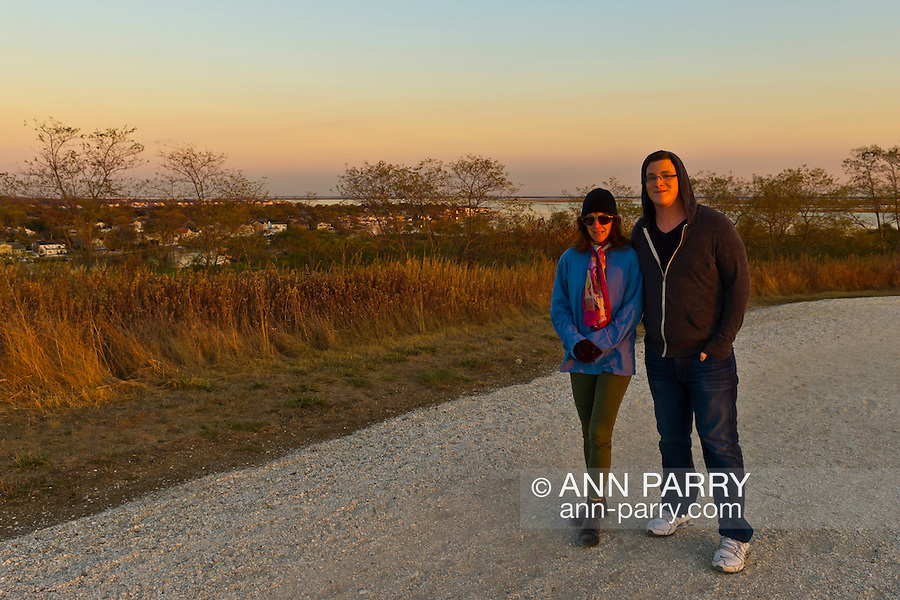 South Merrick, New York, U.S. 29th October 2013. Greg, from Merrick, and his mother Marla walk on the trail through Levy Park and Preserve during sunset on the First Anniversary of Superstorm Sandy hitting New York. A year ago, in the opposite of this peaceful scene, Greg was in one of the houses across the bay in the distance, working to survive Sandy's destructive force, and his mom was in hard hit Long Beach. Long Island's South Shore marshland park, which closed for months due to Sandy's devastation, shows some recovery from the wind and flood damage inflicted on the entire eastern seaboard of America's East Coast.