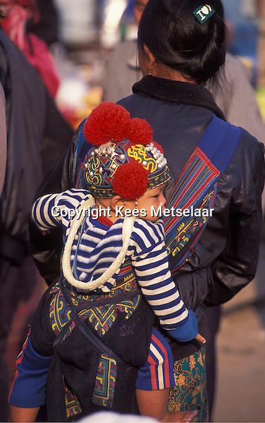 Laos, Luang Namtha Province, Muang Sing..Young Akha kid in her best market dress...Photo by Kees Metselaar, 2003