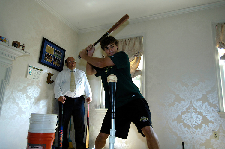 Peter Ferrara watches his son Peter Jr. hit balls in the living room of their house in McLean Virginia ..