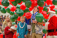 STAFF PHOTO JASON IVESTER --12/16/2014--<br /> Gunnison Riggins (center), 10, watches balloons drop with friends and family on Tuesday, Dec. 16, 2014, during a ceremony inside the Rogers High gym. With support from the school's DECA program, Gunnison's family was given a trip to Hawaii with the Make-A-Wish Foundation. Gunnison has been diagnosed with neuroblastoma.