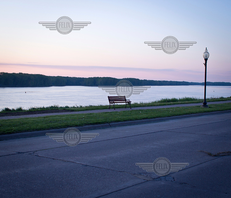 An empty bench at dawn beside the Mississipi River where it flows through Bellvue, Iowa.