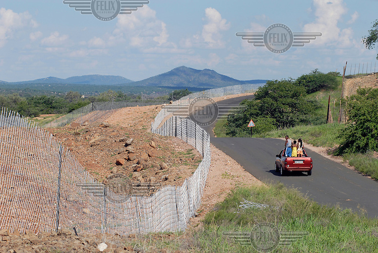 A pickup truck with three passengers standing in the back drives along a road near thr Zimbabwe border. A fence has been built to try and prevent the movement of illegal migrants into South Africa.