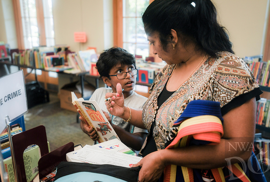 NWA Democrat-Gazette/CHARLIE KAIJO Inesh Vasireddy, 8, of Bentonville (center left) shows Anitha Verneni (right) a book he found during a book sale, Thursday, October 4, 2018 at the Bentonville Public Library in Bentonville.<br /><br />Friends of the Bentonville Library held a soft opening for their annual fall book sale. Members enjoyed early access to the sale. The sale will go until Saturday from 10am to 4pm at the Walmart community room.
