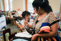 NWA Democrat-Gazette/CHARLIE KAIJO Inesh Vasireddy, 8, of Bentonville (center left) shows Anitha Verneni (right) a book he found during a book sale, Thursday, October 4, 2018 at the Bentonville Public Library in Bentonville.<br />
