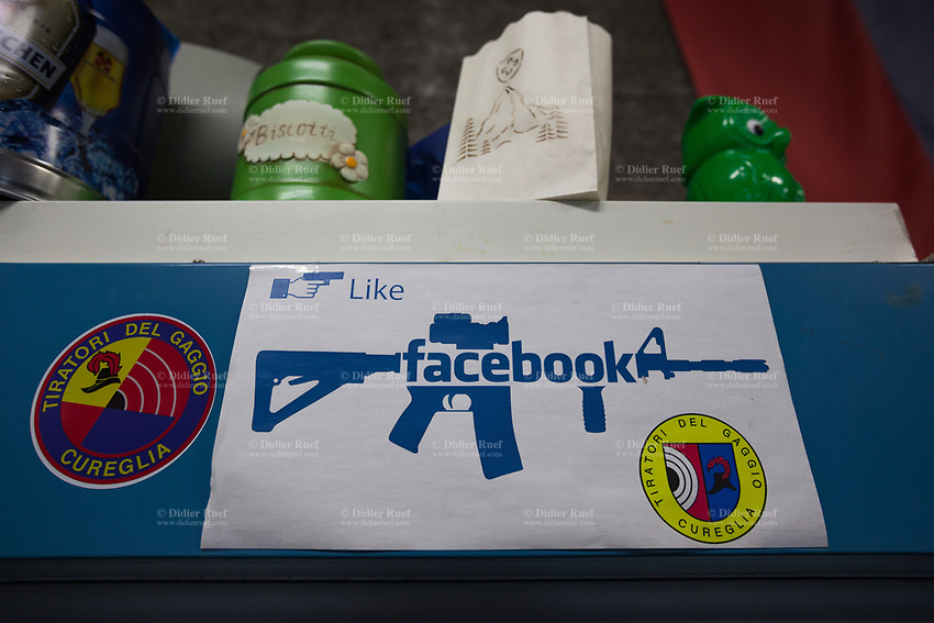 """Switzerland. Canton Ticino. Cureglia is a municipality in the district of Lugano. """"Tiratori del Gaggio"""" society. Shooting range. A modified Facebook social media sign. The """"I like"""" sign with a hand holding a pistol and the Facebook logo on an assault rifle SG 550, also called Fass 90. The SG 550 is an assault rifle manufactured by Swiss Arms AG (formerly Schweizerische Industrie Gesellschaft) of Neuhausen, Switzerland. """"SG"""" is an abbreviation for Sturmgewehr, or """"assault rifle"""". The rifle is known as the Fass 90 or Stgw 90. An assault rifle is a selective-fire rifle that uses an intermediate cartridge and a detachable magazine. 23.02.2019 © 2023 Didier Ruef"""