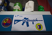 "Switzerland. Canton Ticino. Cureglia is a municipality in the district of Lugano. ""Tiratori del Gaggio"" society. Shooting range. A modified Facebook social media sign. The ""I like"" sign with a hand holding a pistol and the Facebook logo on an assault rifle SG 550, also called Fass 90. The SG 550 is an assault rifle manufactured by Swiss Arms AG (formerly Schweizerische Industrie Gesellschaft) of Neuhausen, Switzerland. ""SG"" is an abbreviation for Sturmgewehr, or ""assault rifle"". The rifle is known as the Fass 90 or Stgw 90. An assault rifle is a selective-fire rifle that uses an intermediate cartridge and a detachable magazine. 23.02.2019 © 2023 Didier Ruef"