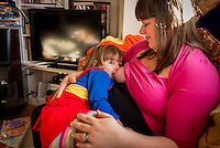 A woman  7 months pregnant breastfeeds her little girl aged nearly 3 years old on the sofa in her living room. the little girl is looking at the camera.<br /> <br /> Image from the &quot;We Do It In Public&quot; documentary photography project collection: <br />  www.breastfeedinginpublic.co.uk<br /> <br /> Dorset, England, UK<br /> 14/02/2013