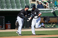 Corey Zangari (14) of the Kannapolis Intimidators slaps hands with third base coach Cole Armstrong (33) after hitting a home run against the Delmarva Shorebirds at Kannapolis Intimidators Stadium on April 13, 2016 in Kannapolis, North Carolina.  The Intimidators defeated the Shorebirds 8-7.  (Brian Westerholt/Four Seam Images)