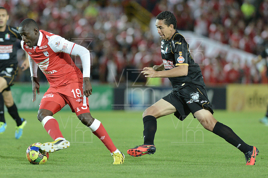 BOGOTÁ -COLOMBIA, 22-06-2013. Cristian Martínez (I) de Santa Fe disputa el balón con Jamell Ramos (D) de Once Caldas durante partido en los cuadrangulares finales, fecha 3, de la Liga Postobón 2013-1 jugado en el estadio el Campín de la ciudad de Bogotá./ Santa Fe player Cristian Martinez (L) fights for the ball with Once Caldas player Jamell Ramos (R) during match of the final quadrangular 3th date of Postobon  League 2013-1 at El Campin stadium in Bogotá city. Photo: VizzorImage/STR