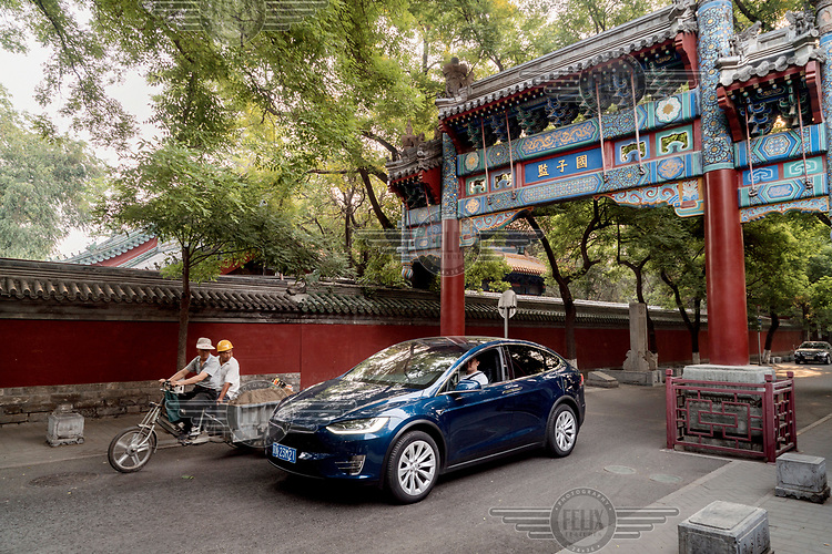 Mike (Fan Wenbo) drives his Tesla Model X through an arch in a traditional 'hutong' alley near Lama Temple.