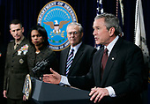 """Arlington, VA - January 4, 2006 -- United States President George W. Bush speaks, calling 2005 a """"year of progress"""" in Iraq, as (L-R) Chairman of the Joint Chiefs of Staff General Peter Pace, Secretary of State Condoleezza Rice and Secretary of Defense Donald Rumsfeld look on January 4, 2006 at the Pentagon in Arlington, Virginia. Bush was at the Pentagon for a briefing on the war by top commanders. He also offered condolences to the families of the 12 West Virginia miners who were found dead after a frantic rescue effort following an explosion at the Sago mine January 2, 2006.<br /> Credit: Alex Wong - Pool via CNP"""