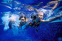Two young girls swim underwater in a blue ceramic tiled pool on Oahu.