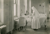Nurse treating a patient in the Salle Saint-Michel in the Precieux-Sang pavilion, photograph, 1943, in the Musee du Monastere des Augustines, or Augustine Monastery Museum, in Vieux-Quebec or the old town of Quebec City, Quebec, Canada. The monastery was housed in the wings of the Hotel-Dieu de Quebec, a hospital built in 1639. The Historic District of Old Quebec is listed as a UNESCO World Heritage Site. Copyright Fiducie du Patrimoine Culturel des Augustines / Manuel Cohen