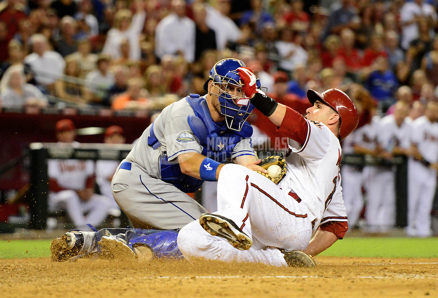 Sept. 11, 2012; Phoenix, AZ, USA: Arizona Diamondbacks base runner Miguel Montero (right) is tagged out at home plate by Los Angeles Dodgers catcher A.J. Ellis in the seventh inning at Chase Field. Mandatory Credit: Mark J. Rebilas-