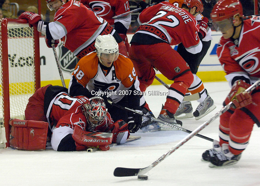 The Carolina Hurricanes' Jeff Hamilton clears the puck after goalie Cam Ward makes a save as the Philadelphia Flyers' Mike Richards falls on him during their game Wednesday, Nov. 21, 2007 in Raleigh, NC. The Flyers won 6-3.
