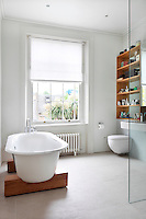 A modern bathroom with a free-standing bath set on two wooden plinths. A wall-mounted shelving unit provides storage space for toiletries.