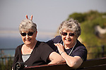 Twin elderly sisters relaxing playfully in a park - EXCLUSIVELY AVAILABLE HERE