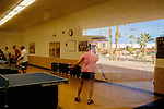 Members of the Sun City Table Tennis Club, including resident Yali Carpenter (left), play games at the Bell Recreation Center in Sun City, Arizona December 1, 2013.
