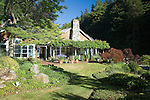 The water and view-facing outside of this wood-shingled, waterfront weekend vacation retreat on Washington State's Vashon Island boasts the large rock chimney, an arbor bearing a massive grape vine that partially shades the brick patio, and curving beds sporting perennials, shrubs, and grasses carved into the lawn.  Windows into the kitchen are to the left, the red-painted door into the center hall can be seen recessed back in, and the windows surrounding the chimney look out from the living room.
