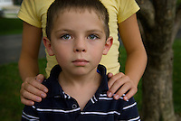 Young boy with sister's hands on his shoulders looks at camera.