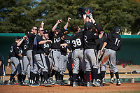 Edgewood Eagles Nick Lehner (36) is mobbed by teammates at home after hitting a home run during the first game of a doubleheader against the Lasell Lasers on April 14, 2016 at Terry Park in Fort Myers, Florida.  Edgewood defeated Lasell 9-7.  (Mike Janes/Four Seam Images)