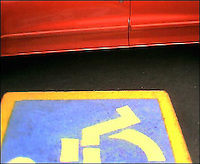 Handicapped parking markings with red car. My Final Photo taken  Nov. 22, 2004.<br /> <br /> Photo Copyright 2004 Gary Gardiner. Not to be used without written permission detailing exact usage. Photos from Gary Gardiner, may not be redistributed, resold, or displayed by any publication or person without written permission. Photo is copyright Gary Gardiner who owns all usage rights to the image. Low resolution photo with watermark.