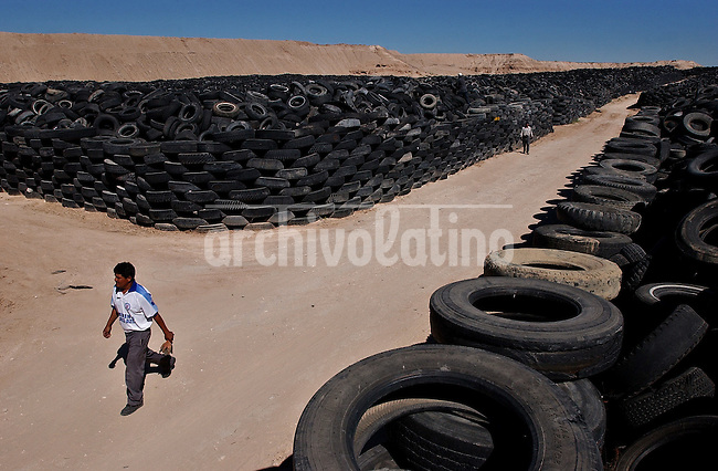 Workers walk at the city's used tires collection center in Ciudad Juarez, Thursday, Sept. 9, 2004. Mexican and U.S. environmental officials said Thursday they will dispose of thousands of tires by burning them for fuel in cement factories, the first step aimed at cleaning up the rusting sedans and mountains of radials cluttering the border.
