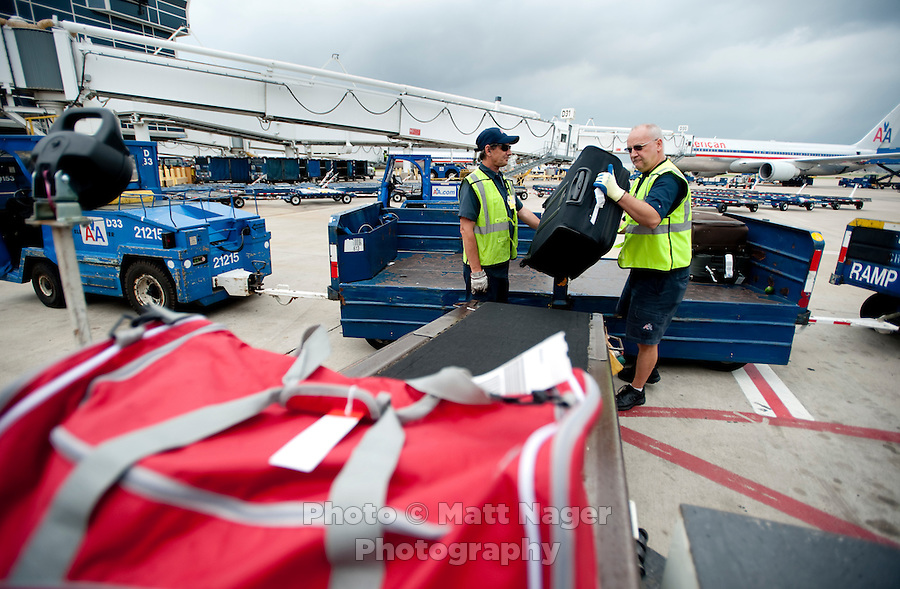 From left, American Airlines Fleet Service Clerks Dave Purdie (cq) and James Webster Jr. (cq) load baggage on a plane at Dallas-Fort Worth International Airport (DFW) in Dallas, Texas, Friday, May 14, 2010. ..PHOTO: MATT NAGER