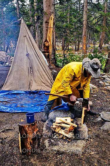 Cowboy building campfire in the rain. Sierra National Forest, California