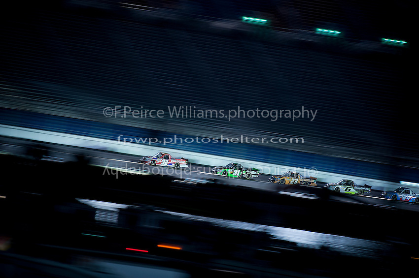 Trucks speed up the back straight past the infield's Lake Lloyd in seasons opening Camping World Truck Series race at Daytona International Speedway. Pictured are Miguel Paludo (#32), James Buescher (#31), Jason White (#23), Justin Lofton (#6) and Max Gresham (#24).