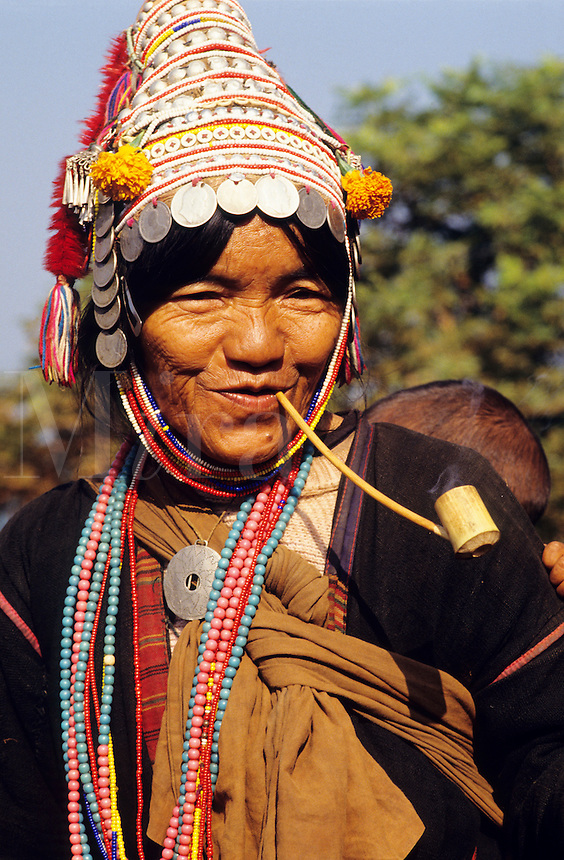 Akha woman, with her baby on her back, smoking a pipe. Northern Thailand..