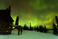 Guests on photo tour at Winter Lake Lodge photograph the Aurora (Northern Lights ) in winter. Lodge buildings in background.    People. taking pictures