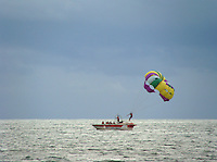 Man on parachute landing on boat at Baga beach,Goa.