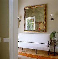 In the entrance hall a 17th century Venetian mirror hangs above a muslin-covered sofa